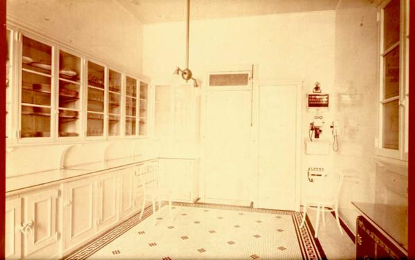 Photo shows the butler's pantry, with walls of glass-front cabinetry, that was the food  service center of the Guggenheim Mansion