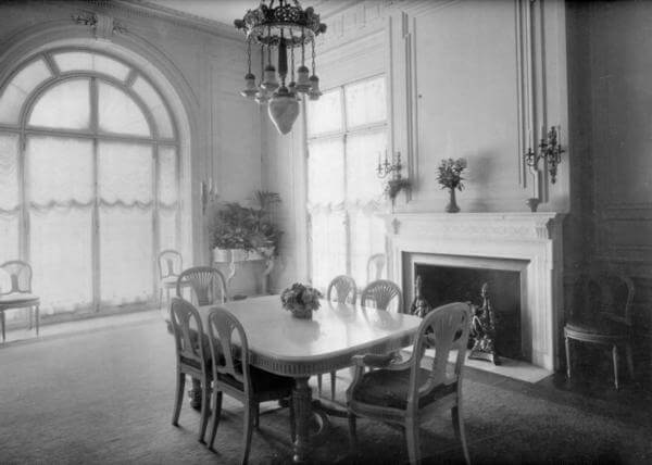 Photo of Guggenheim Mansion's dining room with windows that fill the room with light while French doors provide  access to the covered arcade and breakfast room