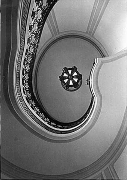Photo shows the winding staircase of the Guggenheim Mansion looking from the ground floor up to the ceiling
