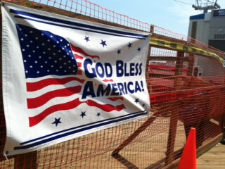 Photo of banner on fence stating God Bless America following Hurricane Sandy